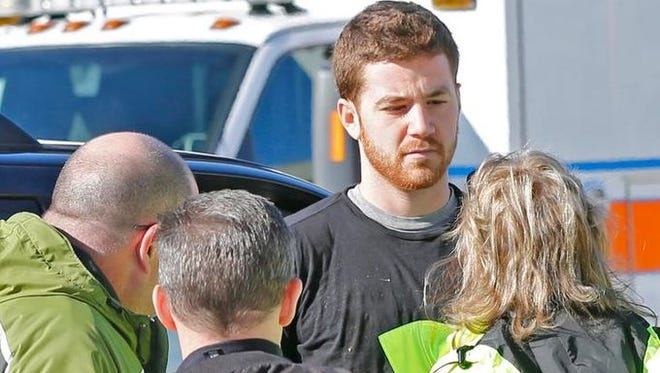 EMS personnel speak Jan. 21, 2014, with Cody Cousins, 23, outside Electrical Engineering building on the campus of Purdue University in West Lafayette, Ind. Cousins was booked into the Tippecanoe County jail on a preliminary charge of murder.