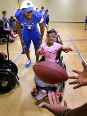 Danielle tosses the football to an MTSU football player as MTSU's Shane Tucker watches over Danielle's during Camp Ability, held each summer.
