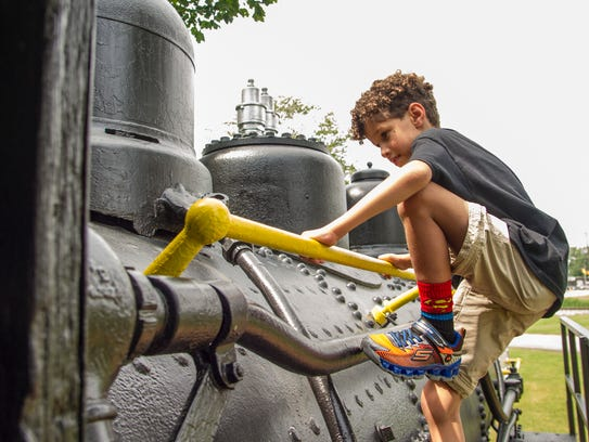 Tristan Saroli, 7, plays on the repainted train at