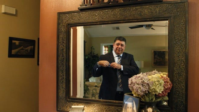Alonso Esposito, a former Boston mobster-turned pastor, checks himself in the mirror before leaving on a recent Sunday for church where he is a minister at Faith Keepers Ministry in Memphis.