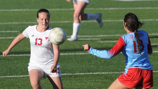 Cooper's Kindyl Wright (13) eyes the ball as Lubbock Monterey's Ashia Sanders defends. Monterey won the District 4-5A game 3-1 on Tuesday, March 20, 2018 at Shotwell Stadium.