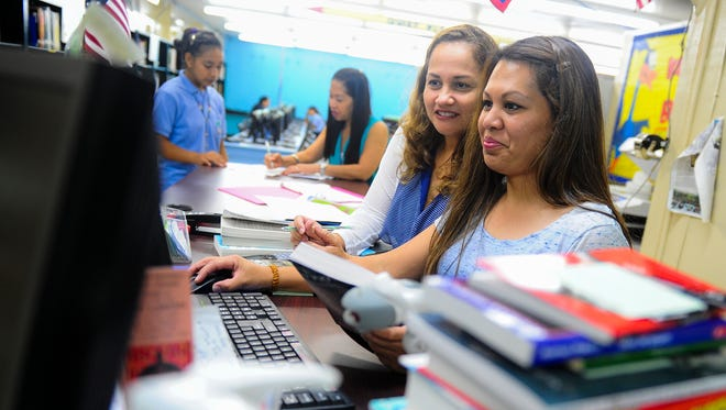 Library Clerk Therese Crisostomo, right, and Library Techinician Louise Togawa logs in new books into the inventory at V.S.A. Benavente Middle School in Dededo on Monday, Aug. 17. Rick Cruz/Pacific Daily News/rmcruz@guampdn.com
