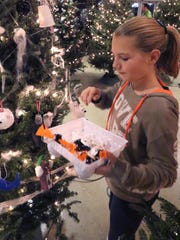 Angel Serocki of Oak Creek Girl Scout Troop 9055 hangs arctic animal ornaments on one of 63 trees in the Fantastic Forest display in the US Bank Gathering Place at the Milwaukee County Zoo on Nov. 29.