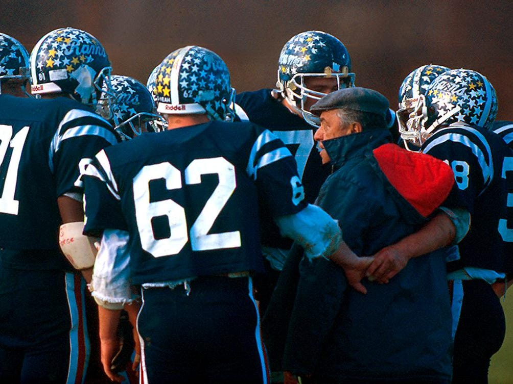 In a photo taken November 11, 1990 at John Bauer Sr's last football game, players gather around the coach for a pep talk during a time out. Bauer, the legendary Ram coach for 25 years, passed away 17 days before the championship game vs. Montclair. He was replaced by his son, John Bauer Jr.