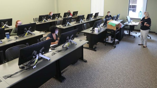 Helen Mandalinich, right, leads a computer applications for professionals class at Stark State College Tuesday, Aug. 4, 2020 in North Canton, Ohio. Students are spaced at least 6 feet apart following COVID-19 protocols.
