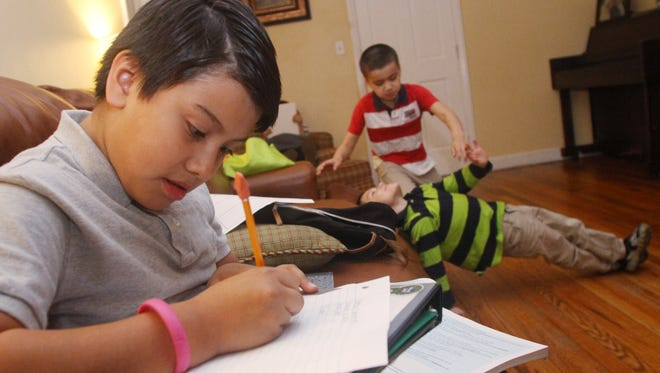 Christian Carrero, age 9, works on his vocabulary homework while his brothers, Fernando, 5, and Eduardo, 6, play in the background, Wednesday, December 2, 2015, in Plainfield.
