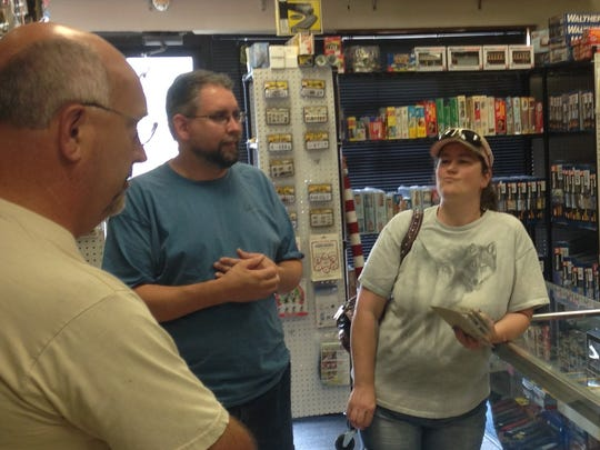 Customers Jim Simpson, Paul Olson and Samantha May confer with Dan's owner Randy Reece.