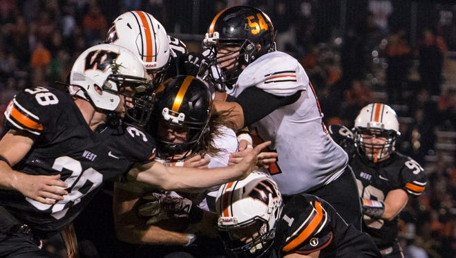 Waverly running back Drew Kritzwiser is brought down by a host of Portsmouth West defenders during the third quarter of Friday's contest at Portsmouth West High School. The Tigers fell to the Senators in SOC action, 31-27.