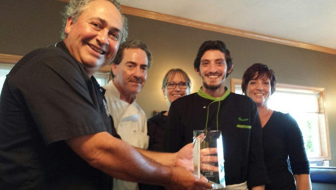 Dave Schuh, of Red Cabin at Green Acres poses with his staff and their award.
