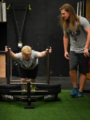 Special olympian Eric Wilson pushes a prowler across