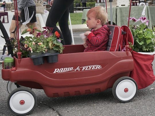 William Verrill, almost 2 years old, shares his wagon with flowers on the opening day of the Plymouth farmer's market. He's there with mom, Brandy Verrill, dad Tom Verrill, and 3-year-old sister Margaret Verrill in this file photo.