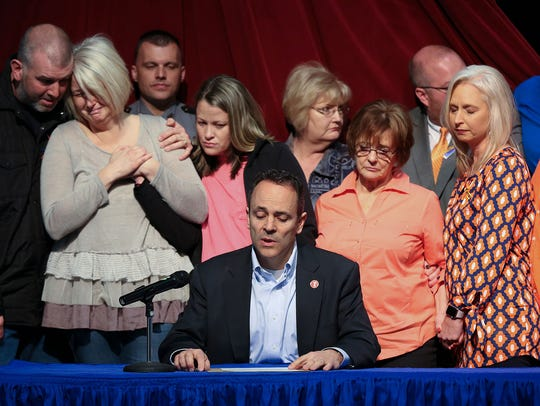 Kentucky Gov. Matt Bevin, center, offers a statement of support for the victims of the Marshall County High School shooting as family members became emotional behind him. They were at the Children's Arts Center in Benton, Ky., on Jan. 26, 2018.