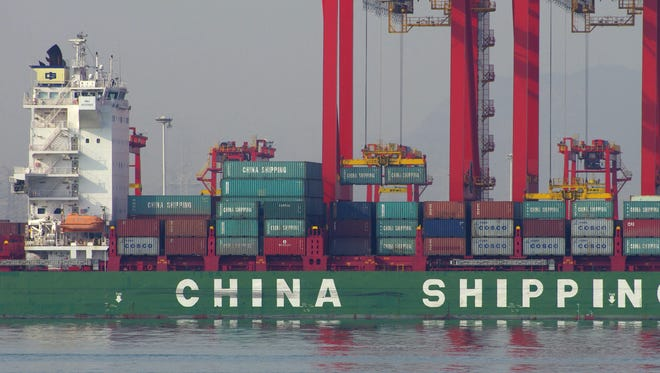 This photo taken on December 6, 2015 shows containers being unloaded from a cargo ship at a port in Rizhao, east China's Shandong province.