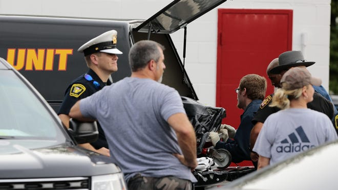 A man's body is loaded into a coroner's unit truck as police respond the scene of an apparent heroin overdose in Avondale this summer. Most do not realize the dangers to which firefighters and police officers are exposed in the heroin crisis, letter writer Jack Degano says.