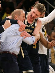 Michigan Wolverines forward Moritz Wagner and head coach John Beilein react after defeating the Purdue Boilermakers in the championship game of the 2018 Big Ten Tournament at Madison Square Garden in N.Y.