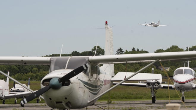 A place takes off in the background at Newport State Airport.