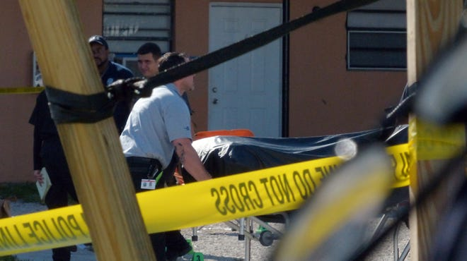 The body of a victim is moved from the scene after a shooting early June 24.