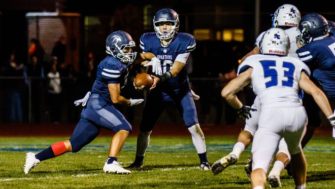 Brookfield East senior Justin Parbs (left) takes a handoff from quarterback Sam McGath (10) during the game at home against Brookfield Central on Friday, Sept. 29, 2017.