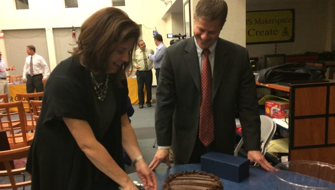Cedar Grove Board of Education member Pam Burke cuts the cake with Superintendent of Schools Michael Fetherman to celebrate her time with the board at a Tuesday, Dec. 6, 2016 meeting in Memorial Middle School.