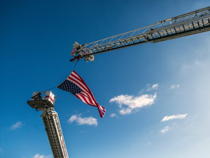 Ladders hold up a flag over 12th Street in front of