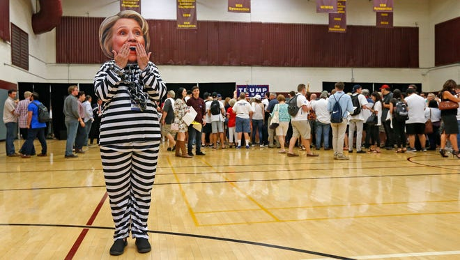 Supporter of Republican presidential candidate Donald Trump, Beth Lyerla of Gilbert, Ariz., wears a Hillary Clinton mask and a prison outfit as she waits for Donald Trump Jr. to speak at a campaign rally for his father at Arizona State University Thursday, Oct. 27, 2016, in Tempe, Ariz. (AP Photo/Ross D. Franklin)