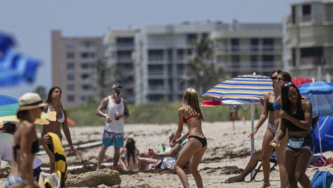 Beachgoers enjoy the sun and sand Monday on Lake Worth Beach. Due to the rise in coronavirus cases, Palm Beach County will close beaches Friday to help fight the spread of the disease.