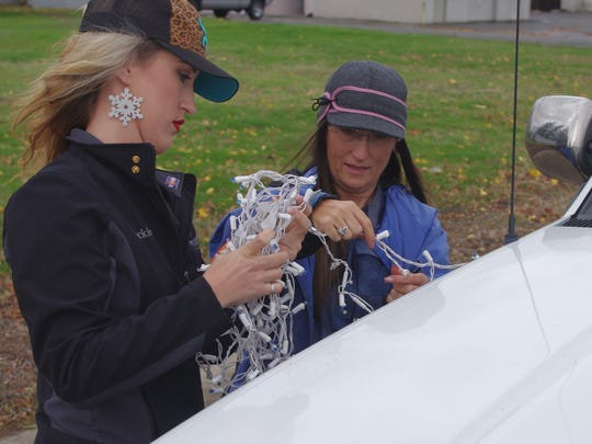 Jackie Scarry, left, and her mom, Janet Scarry tape Christmas lights on a pickup in preparation for the Anderson Lighted Christmas Parade on Sunday.