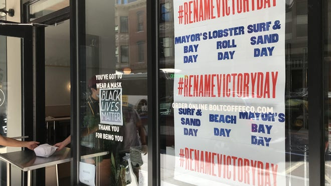 A poster in the window of Bolt Coffee on Washington Street in Providence calls for a new name for what is now the Victory Day holiday.