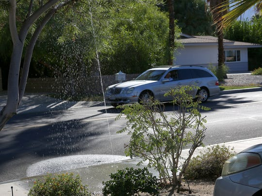 A broken sprinkler head shoots water onto Fairway Drive, just east of Portola Avenue in Palm Desert, on Oct. 26, 2015.