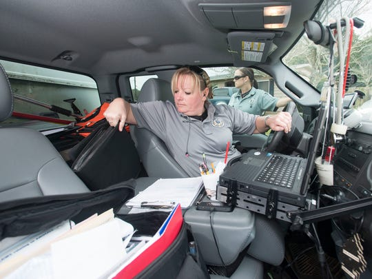 Escambia County Animal Control Officer Sgt. Stephanie Nowlin, left, consults with fellow officer, Jeanette Eriksen, right, while she uses her county vehicle as an office to complete paper work between calls.