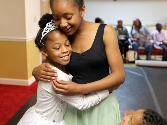 Joia Ubia, 9, left, gives dancer Sarah Elliott, with the Cary Ballet Company, a hug after Plie All Day, an outreach program that hopes to bring dance to women's shelters throughout the Triangle, on April 20, 2017 at the women's shelter for the Durham Rescue Mission.