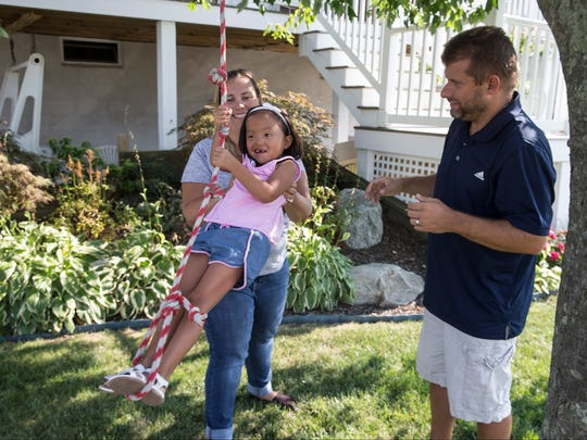 Billy and Catrina Nowrey of Ewing play with their daughter Ramona at a friends house. The Nowrey's adopted Ramona from China, she, like her parents, are deaf. 