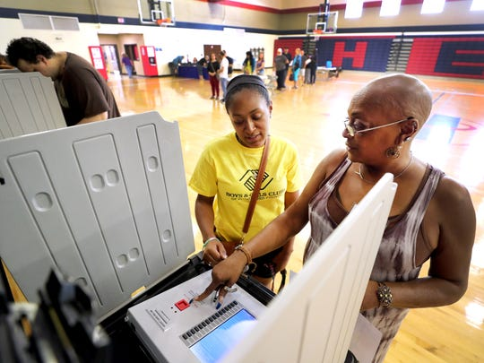 Yolanda Sharp, right, shows Tiara Battle the voting machines before Battle casts her vote at Hobgood Elementary in Murfreesboro, Tenn., on election day, Thursday, Aug. 2, 2018.