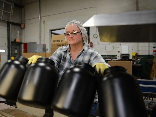 NEW Plastics machine operator Amanda Klemik pulls freshly made plastic bottles from the machine output line before boxing them Dec. 9.