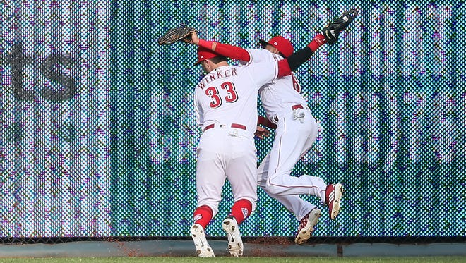 Cincinnati Reds right fielder Jesse Winker (33) and Cincinnati Reds center fielder Billy Hamilton (6) collide in the outfield in the sixth inning during the Opening Day National League baseball game between the Washington Nationals and the Cincinnati Reds, Friday, March 30, 2018, at Great American Ball Park in Cincinnati.