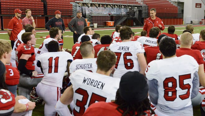 Head coach, Bob Nielson talks with his team after the USD spring football game Saturday at the DakotaDome, April 23, 2016. The defense (red) beat the offense (white) 68-65.