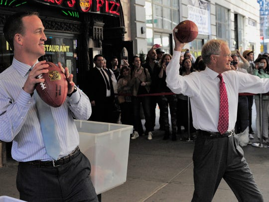 Peyton Manning and David Letterman try their passing skills at moving New York City cabs with open windows.