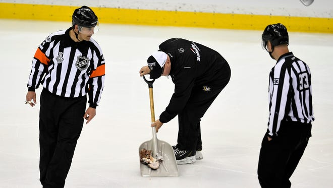 A Penguin worker scoops up the catfish during the second period of game 1 in the Stanley Cup Final at PPG Paints Arena  Monday, May 29, 2017, in Pittsburgh, Pa.