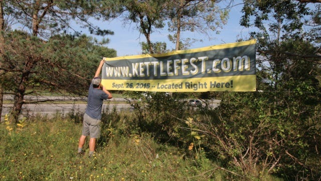 Chris Hurley hangs a sign for KettleFest at Kettle Ridge Farm in Victor.