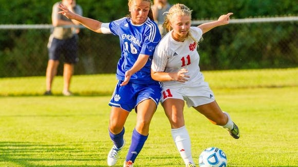Memorial's Grace Lensing (17) goes up for a header opposite Mater Dei's Sunny Lehman (7) Saturday, Aug. 15, 2015, during SIAC soccer jamboree during a EVSC fields in Evansville, Indiana.
