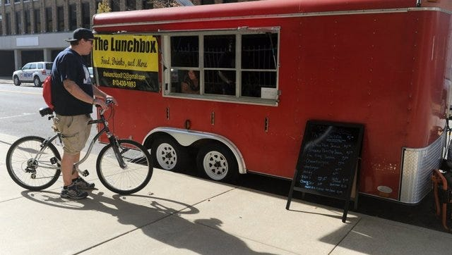 FILE PHOTO — Nichloas Hoagland stops to chat with The Lunchbox co-owner Kirsta Johnson while checking out the menu along Third Street in Downtown Evansville in this 2014 file photo. The food vendor was the first to take part in a pilot program for food trucks in Evansville.