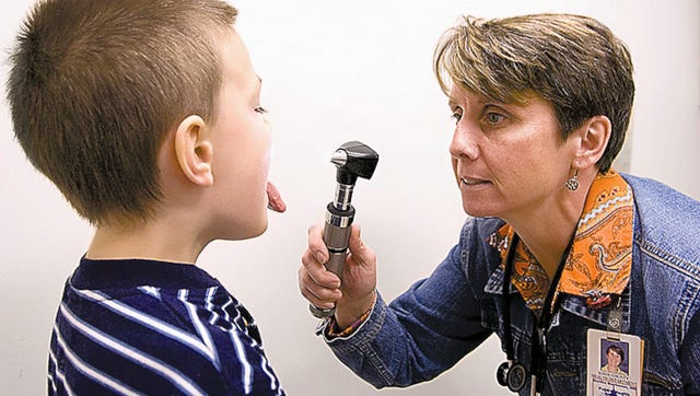 Public health officer Dr. Martha Buchanan examines 5-year-old Nathaniel Lee during a check-up on Monday, Oct 19, 2009 at the Knox County Health Department.
