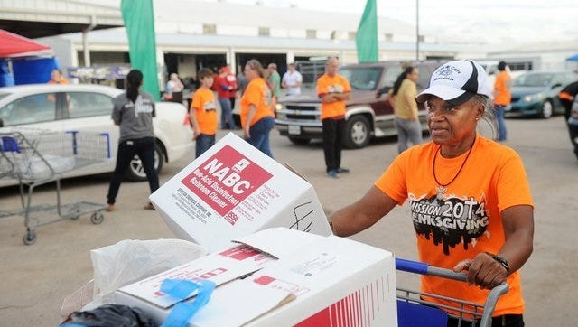 Love & Care Ministries volunteer Fay McGlotten moves donations down to packing trucks during Mission: Thanksgiving in 2014.