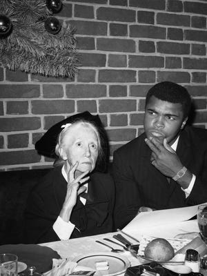 Heavyweight champion Muhammad Ali and poet Marianne Moore, 79, pause at Toots Shor?s Restaurant in New York, Dec. 21, 1966, as they join together in composing poetry about Ali?s title defense against Ernie Terrell. Ali will meet Terrell on February 6, in the Astrodome in Houston, Texas for the championship. (AP Photo/John Lindsay)