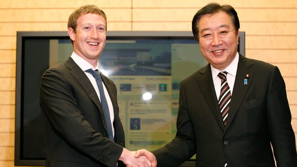 Facebook CEO Mark Zuckerberg (L) shakes hands with