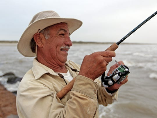 Abel Leal reels in another redfish from the north jetty.