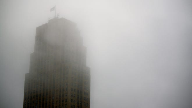 Fog surrounds the Carew Tower early Saturday morning. Temperatures on Saturday are expected to drop from 57 degrees to 17 by the end of the day Sunday.