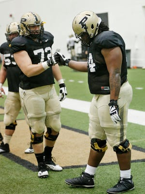 Offensive linemen Jason King, left, and Martesse Patterson shakes hands during spring football practice on March 31, 2016, inside the Mollenkopf Athletic Center at Purdue University.