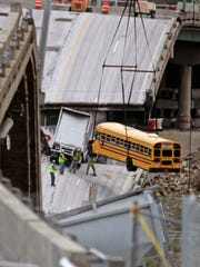 Workers remove a school bus from the interstate 35W bridge collapse site in 2007 in Minneapolis. The school bus was carrying 52 children from a visit to a water park when it dropped with the bridge during the collapse. All the children survived the fall.