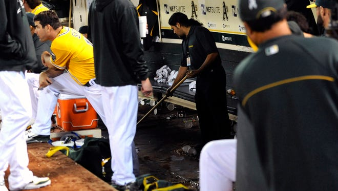 Oakland Athletics clean up crew mop the deck of the dugout after the bathroom overflowed during the seventh inning.